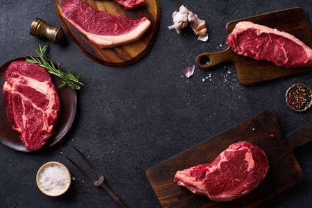 Flat lay variety of fresh Black Angus Prime raw beef steakes: ribeye, striploin, chuck roll and picanha on cutiing boards frame copy space