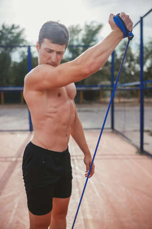 gripper: strong athletic guy pulls blue gripper arms in the open air Stock Photo
