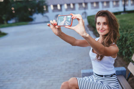 slob: young brunette woman in a park doing selfie Stock Photo