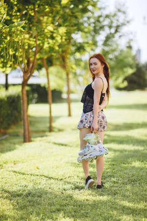 sky scraper: red-haired woman in roller skate in a city park on her T-shirt and bright blue chert in the park grow spruce lined road pavement Stock Photo