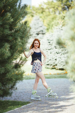 red-haired woman in roller skate in a city park on her T-shirt and bright blue chert in the park grow spruce lined road pavement Stock Photo