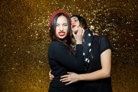 black lesbian: two women dressed black lesbian girlfriends having fun in night clubs photographed on gold background one girl wearing red knit cap and another black scarf with stars them red lipstick and they are very funny and passionate love each other