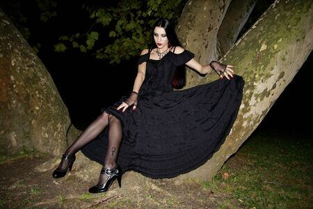 sexy gothic girl standing next to tree