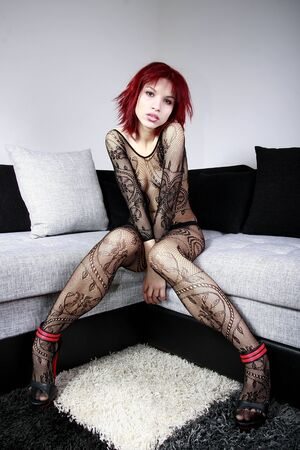 Beautiful redhead model in body stockings on the couch  photo