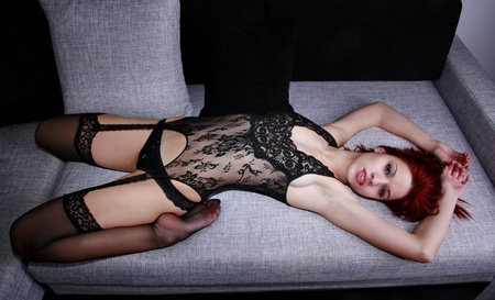 Beautiful redhead model in body stockings on the couch
