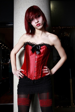 Beautiful redhead model wearing a red corset  photo