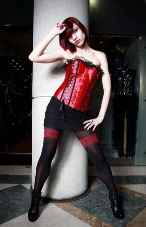 Beautiful redhead model wearing a red corset