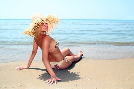 Young model with sunhat relaxing at the beach photo