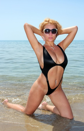 Young blond model with sexy swimsuit at the beach photo
