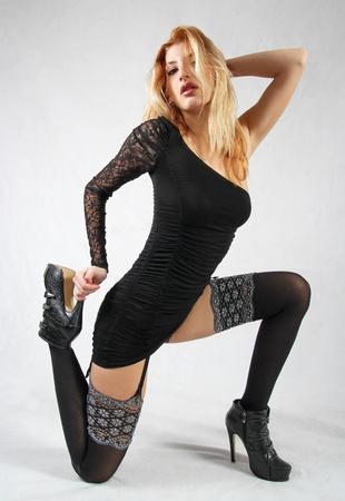 Blond fetish model in sexy black stockings Stock Photo