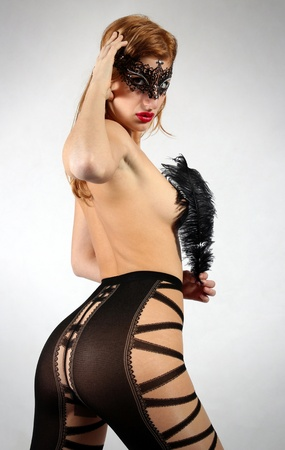 Blond fetish model with mask and feather