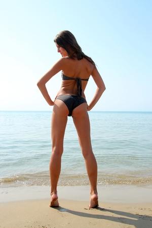 Gril at the beach in black bikini