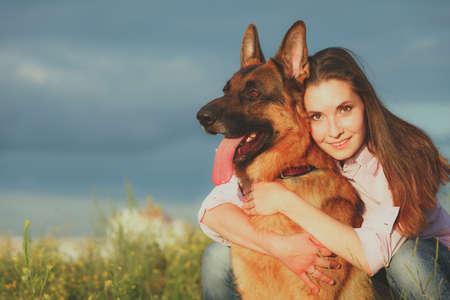 pastor: Muchacha hermosa joven con un pastor alemán que juega en el césped en el tiempo del día