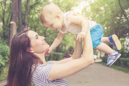 mujeres y niños: Feliz madre jugando con su bebé en el parque en el banco en el momento día