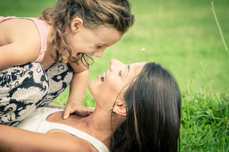 friends hugging: Mother and daughter playing on the grass at the day time. Concept of friendly family. Stock Photo