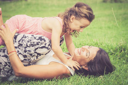 Happy mother and daughter playing in the park at the day time. Concept of celebration Mothers day . Stock Photo