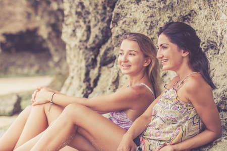 amistad: Bastante hermosa morena y amigos de la chica rubia que se divierten. Tanto sentado en la playa y sonriente riendo. Concepto de la amistad femenina.