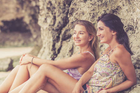 women friendship: Pretty beautiful brunette and blonde girl friends having fun. Both sitting on the beach and smiling laughing. Concept of female friendship.