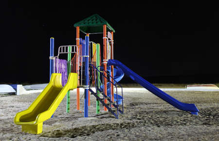 A colorful empty playground for children with slides at night photo