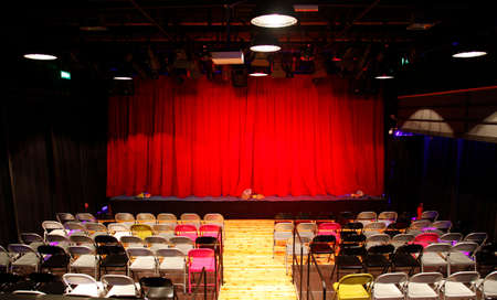Small empty theatre hall with red curtains, stage and number of colorful chairs