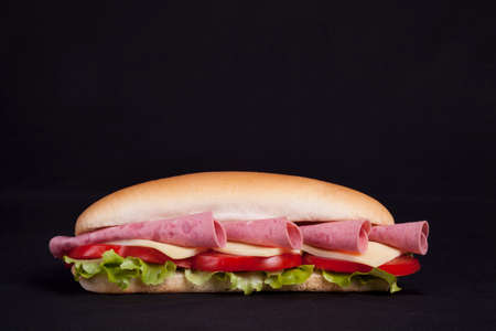 Fresh healthy sandwich with salad, cheese and salami isolated over blac photo