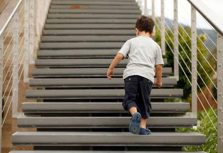 subiendo escaleras: Ni�o que subir las escaleras Foto de archivo