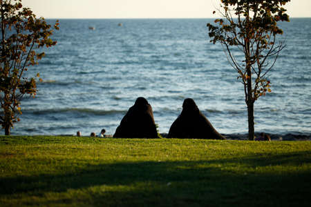 purdah: Two women in full black hijab sitting in a park towards the sea