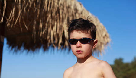 5 year old: Cute 5 year old Caucasian boy poses on a beach in summer wearing sunglasses