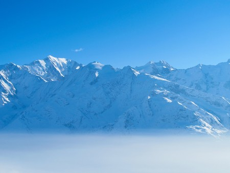 rise above: Snow covered mountains rise above morning mist on sunny day Stock Photo