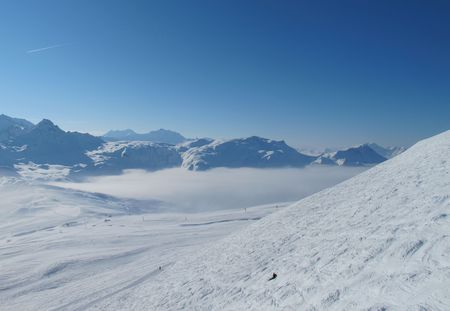 Lone skier in panoramic landscape of snow covered mountains. Skiing Les Contamines, French alps Stock Photo - 8031655