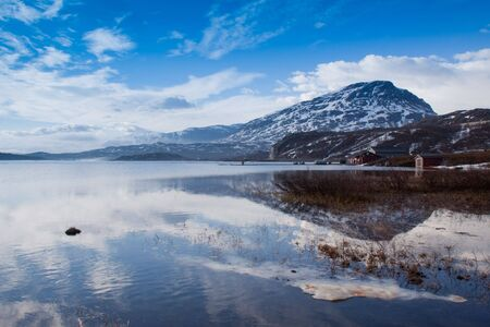 panoramas: Winter mountain reflection in lake on sunny day with blue skies. Riksgransen, Sweden. Stock Photo