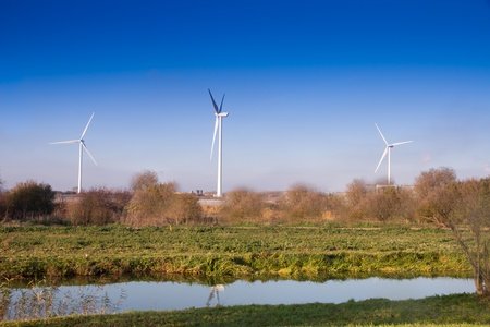 hardwearing: Three Wind turbines in English countryside  on  blue sky autumn day with canal in foreground