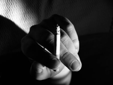 Addiction to smoking. Hand of a man in black and white Stock Photo