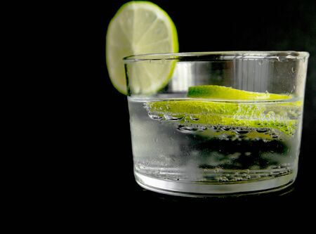 non alcoholic beverage:  tonic with lime fruits isolated in black background