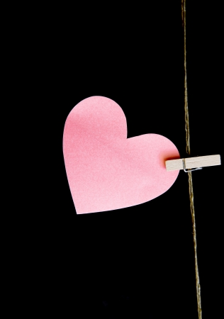 heart with clothespin on black background Stock Photo