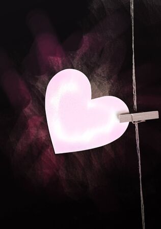 recollections: heart with clothespin on black background Stock Photo