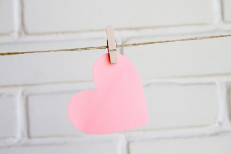 heart with clothespin on white background wall Stock Photo