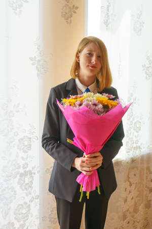 Young lady with bouquet of flowers standing at the window Banque d'images - 95731236