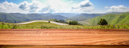 Empty wooden table with blurred panoramic background of summer landscape with road and mountain village. Can be used for display or montage products