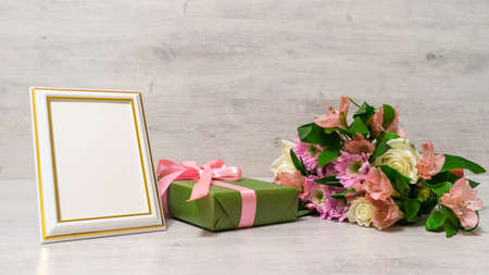 Colorful bouquet of roses, chrysanthemum and alstroemeria flowers with gift box and empty photoframe on wooden background Stock Photo