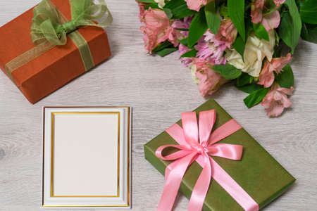 Colorful bouquet of roses, chrysanthemum and alstroemeria flowers with gift boxes and empty photoframe on wooden background