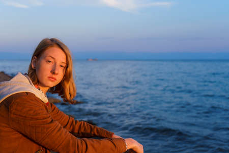 Portrait of young beautiful lady admiring the summer landscape of lake Baikal at sunset