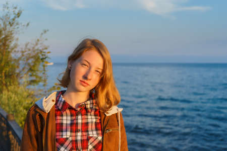 Portrait of young beautiful lady in the summer at sunset on the shore of lake Baikal Stock Photo