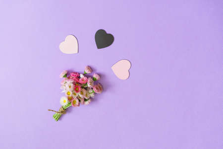 Summer creative composition in minimal style. White and pink Marguerite daisy flowers bouquet with two light hearts and one black heart on lilac background. Top view, flat lay, copy space Stok Fotoğraf