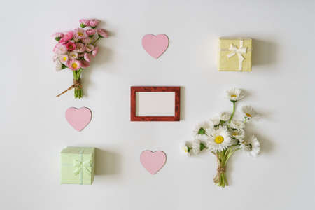 Summer creative composition. White and pink Marguerite daisy flowers bouquets, small gift boxes in pastel colors, pink hearts and empty photoframe on white background. Top view, flat lay, copy space Stok Fotoğraf