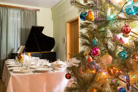 Living room interior with beautiful decorated Christmas tree, festive table and vintage piano. Concept of new year holiday at cozy home