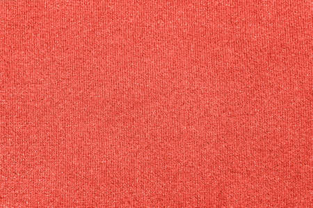 Modern fabric background or mock up with space for text. Texture of cloth with sequins in color of the year 2019 Living Coral Stock Photo