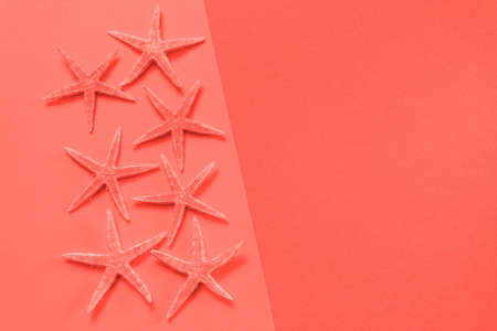 Summer background of living coral paper with starfish, symbolizing the sea coast. Color of the year 2019, copy space Stock Photo