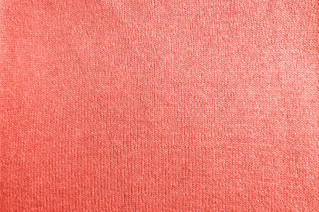 Modern fabric background or mock up with space for text. Texture of knitted jersey in color of the year 2019 Living Coral