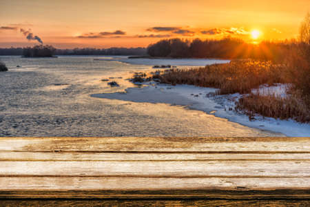 Empty wooden table with blurred picteresque winter background of riverside at sunset. Mock up for display or montage products